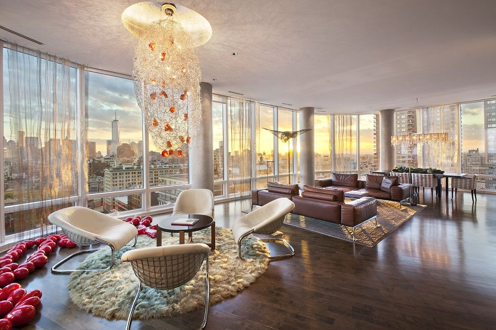 modern looking room of a penthouse overlooking the new york skyline